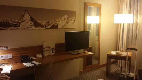 Mövenpick Hotel & Casino Geneva: Desk and small TV  takes up all the space for walking around the bed