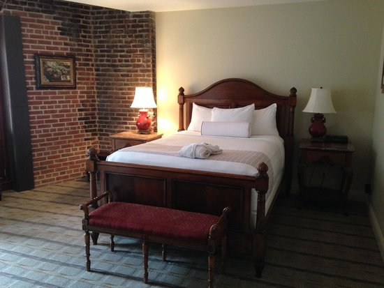 Inn at Henderson's Wharf: The queen bed in our room with exposed brick wall.