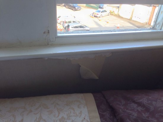 Redcar Hotel: Peeling wallpaper by bed .. And damp around window