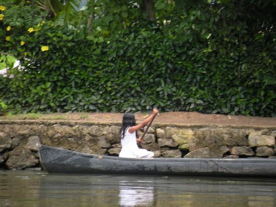 Kerala Backwaters: A child using country boat to roam around