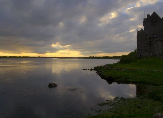 Dunguaire Castle's Medieval Banquet: Castle silhouetted in sunset across the bay