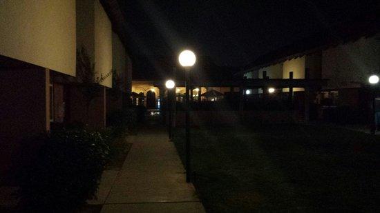 Ramada Fresno North: Courtyard grass area at night looking toward pool