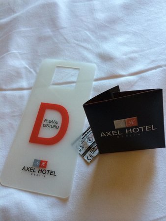 Axel Hotel Berlin: Please disturb sign and condom.. from the hotel..