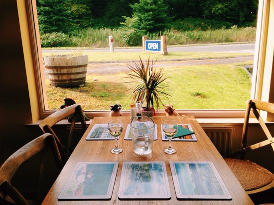 "Oakwood Restaurant : Table by the window with ""open"" sign on the street."