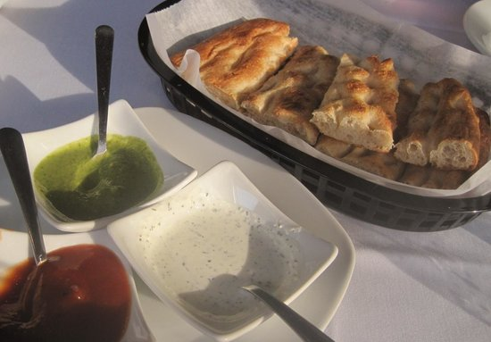 Pomir Grill: Afghan Naan (bread) with three dipping sauces.  We like the green coriander-based sauce the best