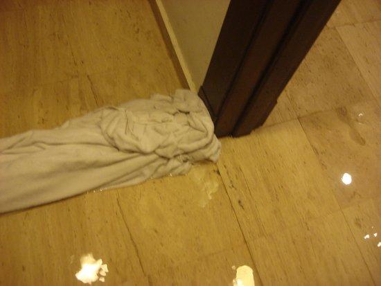 Grand Palladium Vallarta Resort & Spa : Habitación y entrada al baño - tratando de bloquear un poco el agua con las toallas