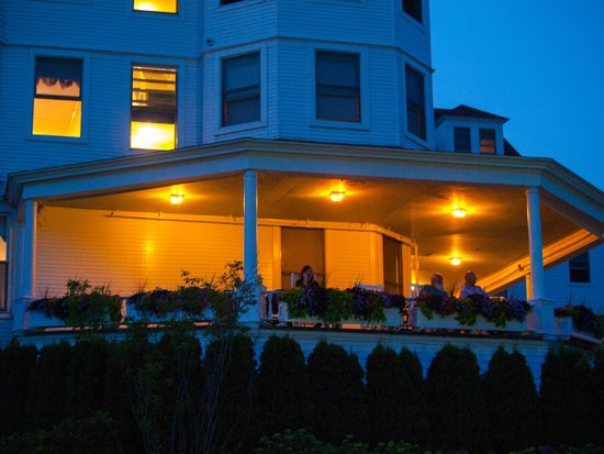 Island House Hotel: Part of the front porch lit at night