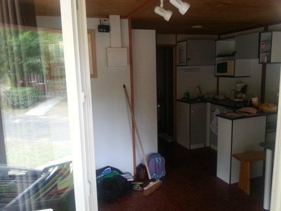 Belambra Clubs - Les Estagnots-Pinède : la cuisine sans rangements, avec son petit banc en bois et sa table pour manger dans le noir