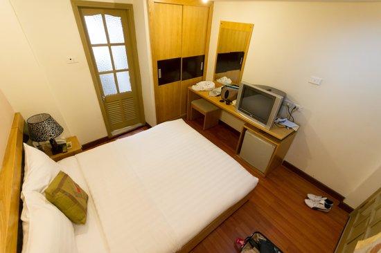 Rising Dragon Hotel: 大きいベッド、奥の扉の向こうにトイレとシャワー