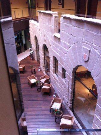 F&G Logrono: zona de lectura o cafe,la imagen es de una muralla que se mantiene dentro del hall.