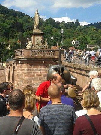 Carl Theodor Old Bridge (Alte Brucke): turista atendiendo explicación sobre el bronce del gato-mono
