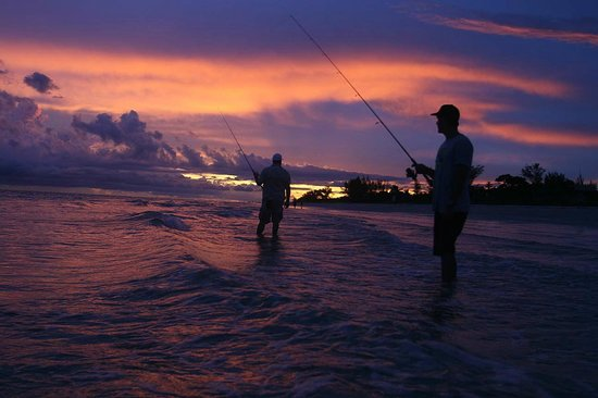 Sunset Beach Inn: Fishing in the surf with a beautiful sunset as a background