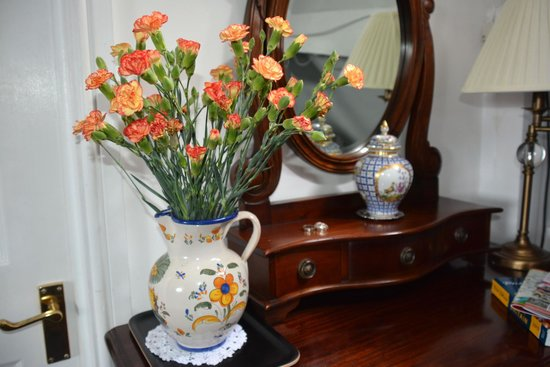 Adelphi Guest House: Flowers and a matching pitcher adorn the antique dresser .