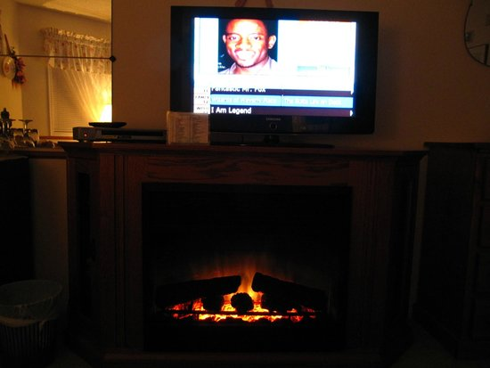 Village Country Inn: Flat screen tv with many channel options, above an electric fireplace for optimum ambience.