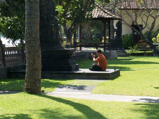 Aditya Beach Resort: Staff member makes offerings in the garden at Aditya