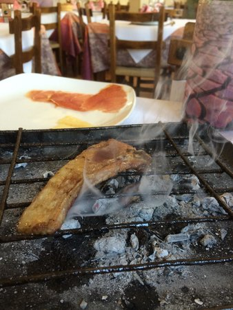 Casa Rural El Mesón: Smoking chops on the table with some amazing Crianza made by the brothers of the family. .. Drea