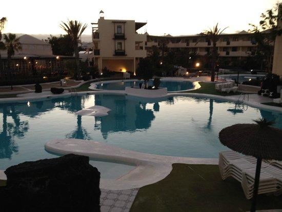 Apartamentos El Trébol : pool area at dusk