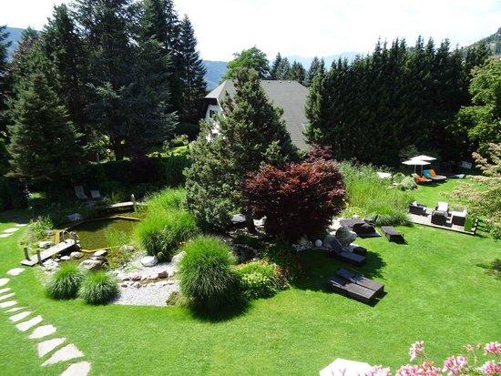 Ferienhotel Trattnig: Blick vom Balkon aus auf einen Schwimmteich im Garten