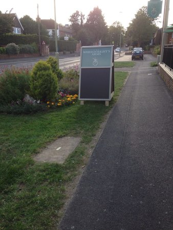 The Wheelwrights Arms: A board on council grass verge blocks vision when leaving car park