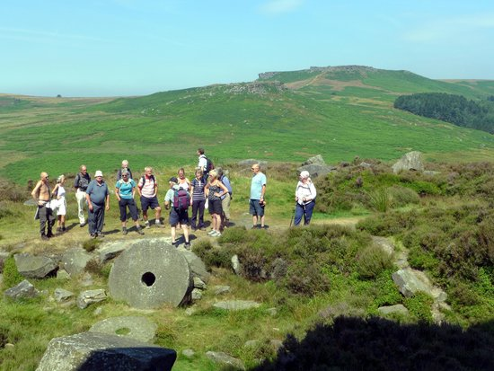Longshaw Estate: The Wednesday free guided walk pause by some millstones to admire the view of Carl Wark and Higg