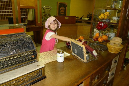 """Walnut Grove, Миннесота: """"Buying"""" items in the hands-on Main Street. Note the post office in the background."""