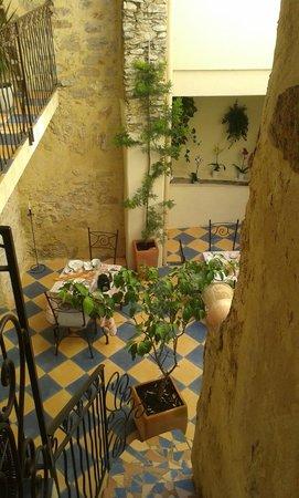 Le Patio : vue du patio en haut de l'escalier avec les tables du petit déj