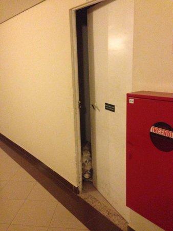 Mercure Santos : Corredor com lixo segurando porta de serviço