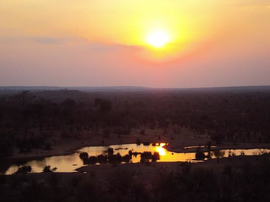 Victoria Falls Safari Lodge: Sunset over water hole at VF Safari Lodge