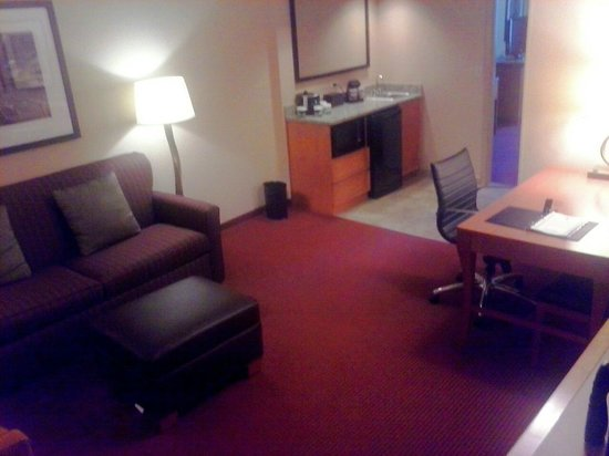 Embassy Suites by Hilton Kansas City-International Airport: Room sitting area w/ couch, chair, desk, and TV.