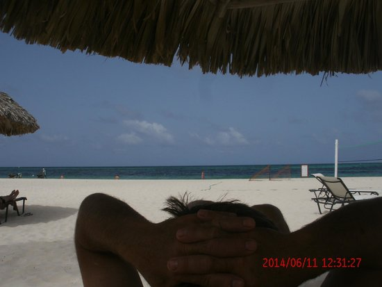 Secrets Royal Beach Punta Cana: Husband lounging at the beach - clean white sand, staff collecting all seaweed -