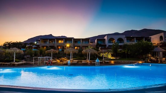 AquaGrand Exclusive Deluxe Resort : The beachfront pool and rooms at dusk