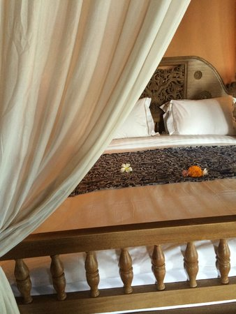 Hotel Tugu Bali: Four-poster bed strewn with frangipane flowers day and night