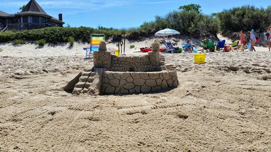 Linger Longer By The Sea : Sandcastle on Beach in front of Apartment Building