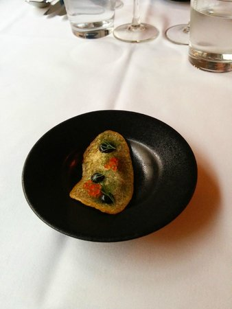 Demo: Amuse-bouche featuring a thin potato crisp with squid ink paste and fish roe