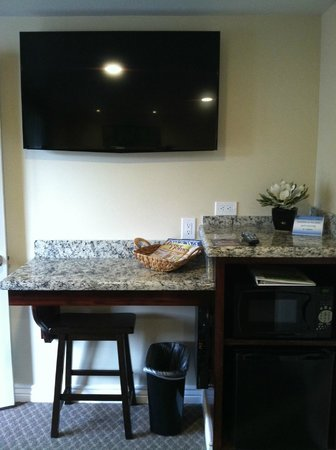 Primrose Inn and Suites: desk with a stool/fridge & micro with flat screen