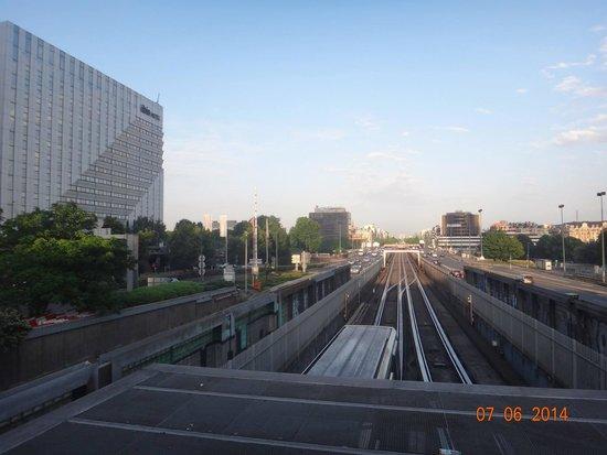 Ibis Paris La Defense Centre : Da estação de metrô La Defense, o hotel à esquerda; no fundo da linha de trem,o Arco do Triunfo