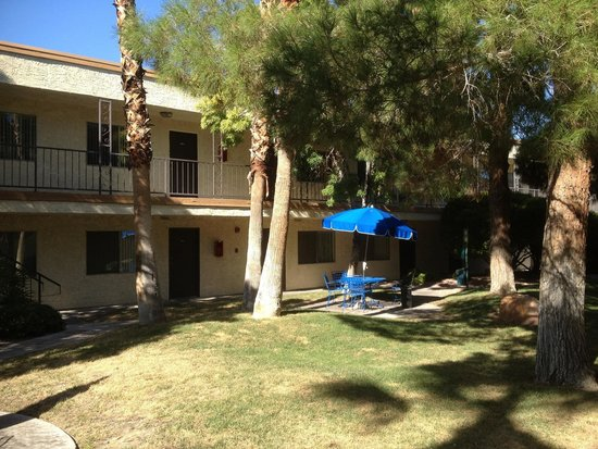 Holiday Royale Apartment Suites: Umbrella picnic tables, palm and pine trees, grass(rare in Vegas)