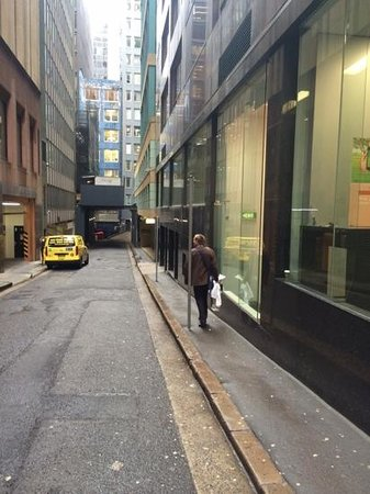 Medina Serviced Apartments Martin Place: Main entrance down a noisy lane with a construction site and busy garbage collecting trucks late