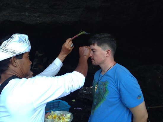 Bali Traditional Tours - Day Tours: Receiving a blessing at Tanah Lot Temple.