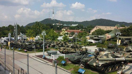 Monumento de Guerra de Corea: Outdoor military equipment exhibition area. N Seoul Tower visible in the distance.