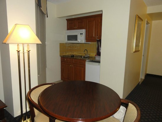 Le Nouvel Hotel & Spa: The kitchenette and table--cooktop, sink, microwave, fridge--stocked with dishes, pots, coffee,