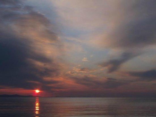 Villa Triana : Por-do Sol em frente ao hotel, sentado à beira mar.