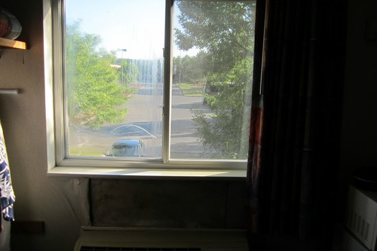 Rodeway Inn : Our room's window with broken glass and some of the missing wallpaper.