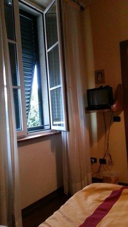 Hotel Melecchi: von Bett auf das doppelt verglaste Fenster mit grünen Läden. Rechts ein kleiner Fernseher.