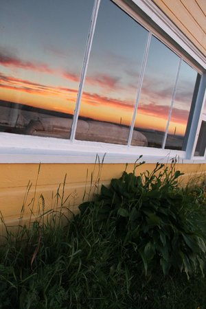 Beach Breeze Motel: Reflection of the sun set it window of cottage