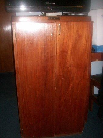 Posadas Hotel: mueble del frigobar todo desvencijado sobre el cual esta el plasma
