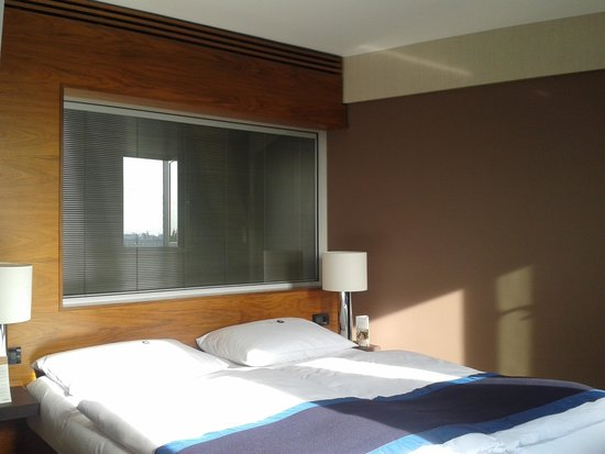 Mövenpick Hotel Hamburg: Bett mit Badezimmerscheibe