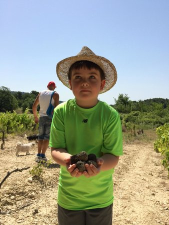 Truffle Hunting at Les Pastras : Our 6 year old in Johann's hat with a handful of truffles.