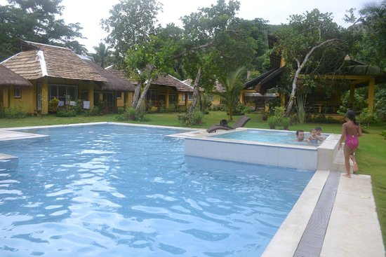 La Natura Resort: pool with jacuzzi with nipa hut houses on the background