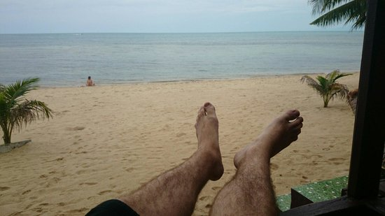 New Hut Bungalows: Descansando na varanda do bangalô enquanto a namorada relaxa na praia.